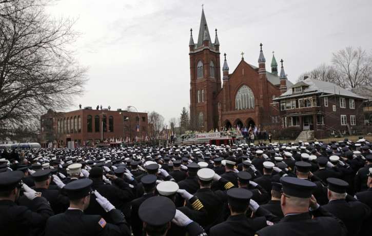 Firefighters salute as the casket of Boston Fire Lt. Edward Walsh is lowered from Engine 33 as it arrives outside the Church of Saint Patrick in Watertown, Mass., Wednesday, April 2, 2014. Walsh and Boston Firefighter Michael Kennedy died after being trapped while battling a fire in Boston. (AP Photo/Charles Krupa)