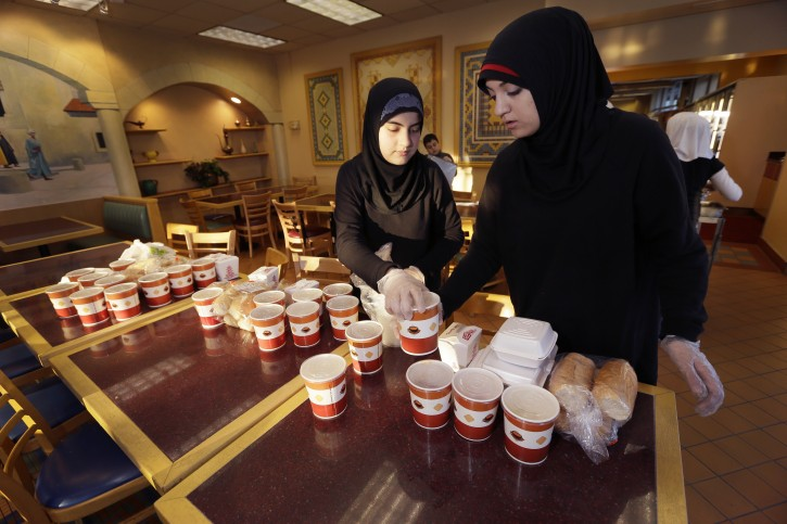 Volunteers Wafaa Dabaja, left, and Zahraa Dabaja, prepare meals from food provided by the Yasmeen Bakery in Dearborn, Mich., Friday, April 25, 2014. The reach of one of the nation's few charitable organizations exclusively providing halal food to the poor could be greatly expanded under the new federal provision. Zaman International Inc. is based in Dearborn, which has a large Muslim population has provided about 250 tons of hot and dry food since 2010 and serves about 150 families with a monthly food box and vouchers. (AP Photo/Carlos Osorio)
