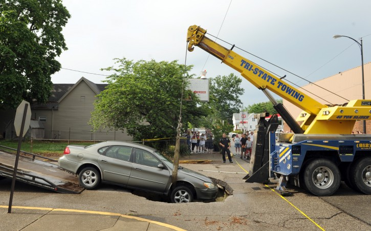 A wrecker lifts a car that fell into a  hole after a water main broke on Oregon St. at Main St. in Evansville, Ind. on Friday, May 30, 2014. The car's owner said he, his girlfriend and two children were in the car at the time. All got out safely from a passenger side door. (AP Photo/The Evansville Courier & Press, Kevin Swank)