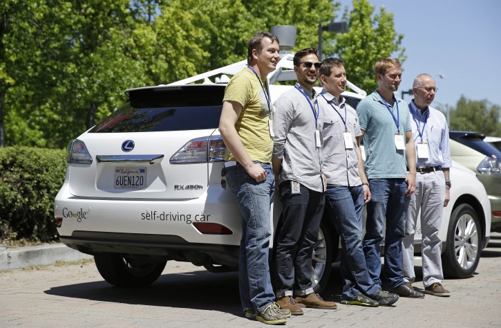 In this photo taken Wednesday, May 14, 2014, Google team members pose by a Google self-driving car at the Computer History Museum in Mountain View, Calif. From left is project direct Chris Urmson, Brian Torcellini, Dimitri Dolgov, Andrew Chatham and Ron Medford, the director of safety for the project. Four years ago, the Google team developing cars which can drive themselves became convinced that, sooner than later, the technology would be ready for the masses. There was just one problem: Driverless cars almost certainly were illegal. (AP Photo/Eric Risberg)
