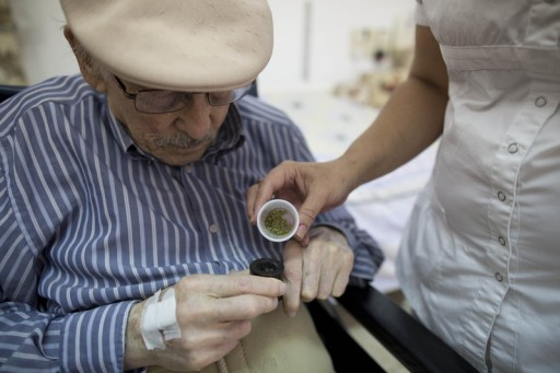 File photo of Holocaust survivor Moshe Roth, 81, receiving medical marijuana by a nurse to smoke in his pipe.  EPA/ABIR SULTAN