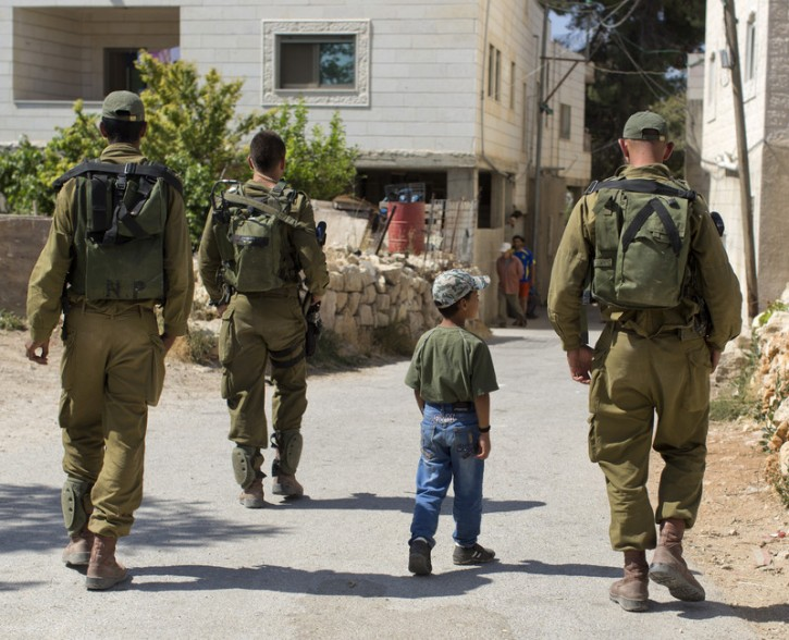 A Palestinian boy joins Israeli soldiers as they walk down a road where soldiers discovered bloodied cloth and a rock, during searches in the hills near the village of Halhoul, just north of the West Bank city Hebron, 22 June 2014. EPA/JIM HOLLANDER