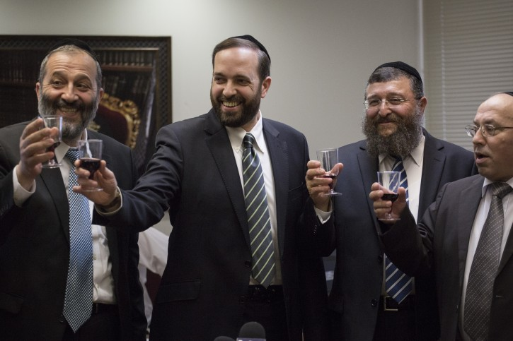 Incoming Member of Knesset, Yoav Ben Tzur (L), outgoing member, Ariel Atias (C), and Shas party chairman, Arye Deri (L), raise a glass to toast the new member, during the Shas Faction meeting that bid him farewell, at the Knesset on June 23, 2014. Photo by Hadas Parush/Flash90