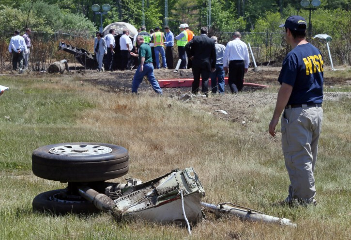 FILE - A National Transportation Safety Board official stands beside a piece of the landing gear at the scene Monday, June 2, 2014, in Bedford, Mass., where a plane plunged down an embankment and erupted in flames during a takeoff attempt at Hanscom Field on Saturday night. Lewis Katz, co-owner of The Philadelphia Inquirer, and six other people died in the crash. (AP Photo/Boston Herald, Mark Garfinkel, Pool)