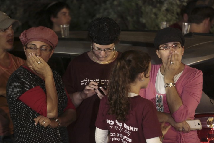 Friends and relatives of Naftali Fraenkel, 16, one of three missing teenagers, gather outside of his home after the announcement his body was found earlier today near the West Bank town of Hebron, at West Bank Jewish settlement of Nof Ayalon, where the Fraenkel family live, Monday, June 30, 2014.  AP