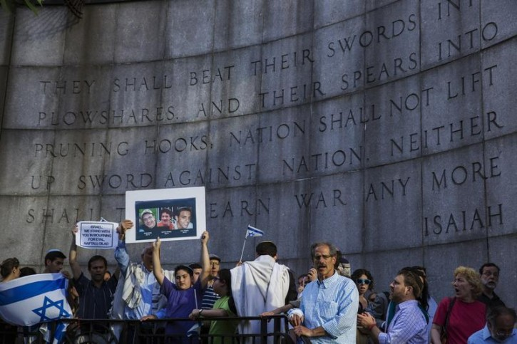 A boy holds a board with the likeness of three teenagers who had been kidnapped in Israel during a memorial service near the United Nations headquarters in New York June 30, 2014.  Reuters