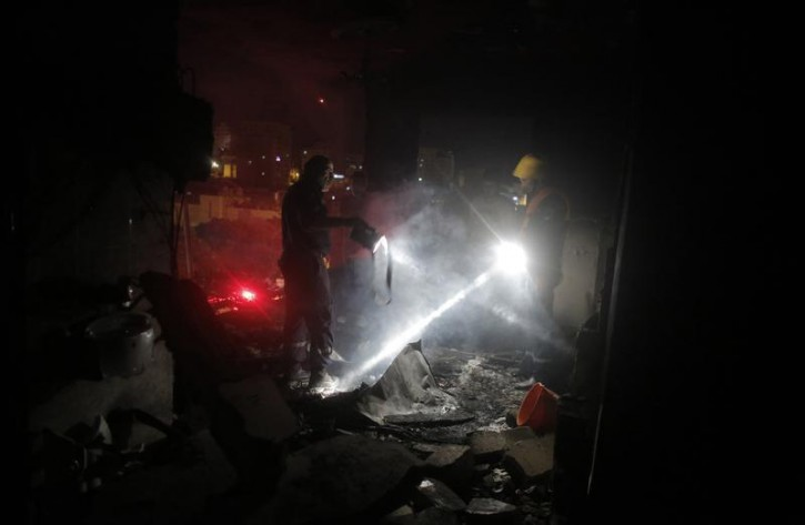Palestinian fire workers inspect the family home of an alleged abductor after a blast in the top floor in the West Bank City of Hebron July 1, 2014.