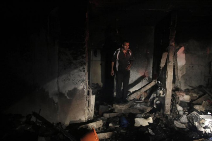 A man inspects the family home of an alleged abductor after a blast on the top floor in the West Bank City of Hebron July 1, 2014.  Reuters