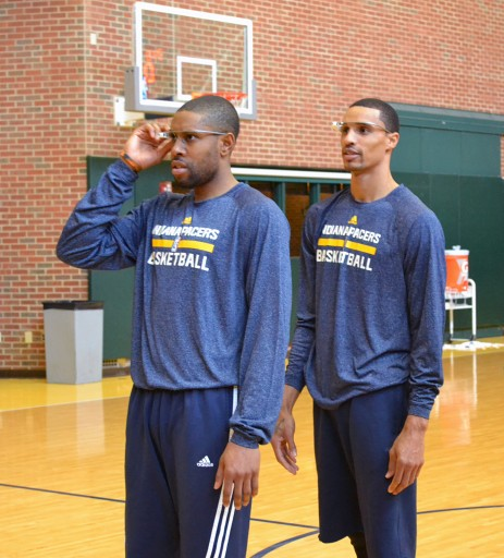 In this March 25, 2014 photo provided by Pacers.com, Indiana Pacers basketball players C. J. Watson, left, George Hill, center, and Lavoy Allen, at right back to camera, wear Google glasses during practice at Bankers Life Fieldhouse in Indianapolis. Google Glass is slowly becoming more common in sports as teams and broadcasters try to bring fans closer to the action. (AP Photo/Pacers.com, Celeste Ballou)