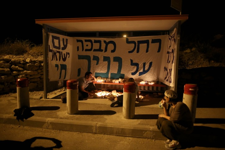 Israelis light candles at the bus stop where the three teenagers were last seen in Gush Etzion, near Hebron, the West Bank, 30 June 2014.  EPA