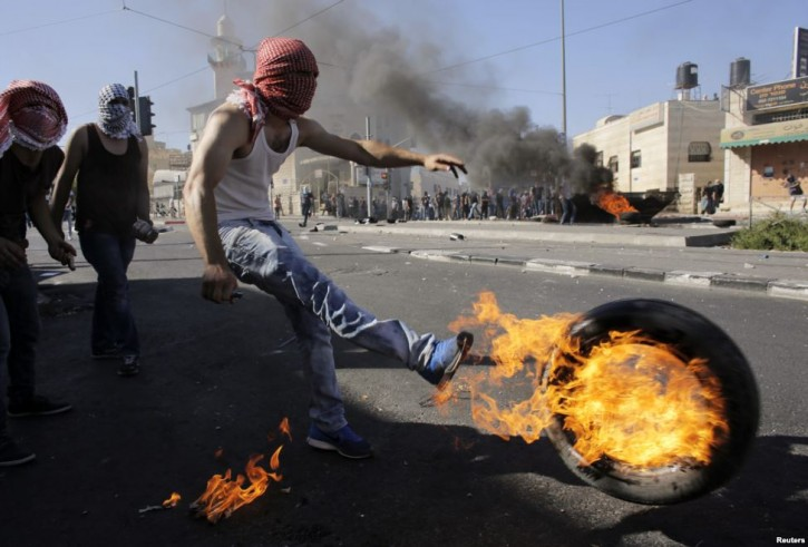 A Palestinian kicks a tire after setting it ablaze during clashes with Israeli police in Shuafat, an Arab suburb of Jerusalem.  (Reuters)
