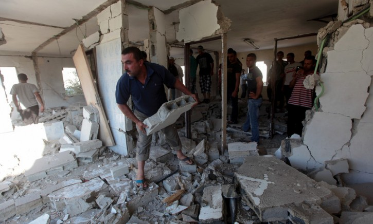 Palestinians inspect the demolished home of Ziad Awad from the West Bank village of Idhna, south of the West Bank city of Hebron, 02 July 2014. EPA/ABED AL HASHLAMOUN