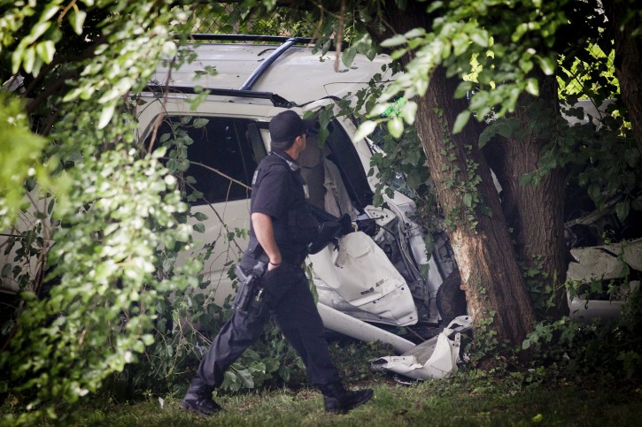 A police officer walks past the wreckage of a carjacked vehicle that police say hit a group of people on a corner in Philadelphia on Friday, July 25, 2014, killing three two children and critically injuring three other people. One of the children was pronounced dead at the scene and another at a hospital, Homicide Capt. James Clark said.  (AP Photo/Philadelphia Daily News, Alejandro A. Alvarez)