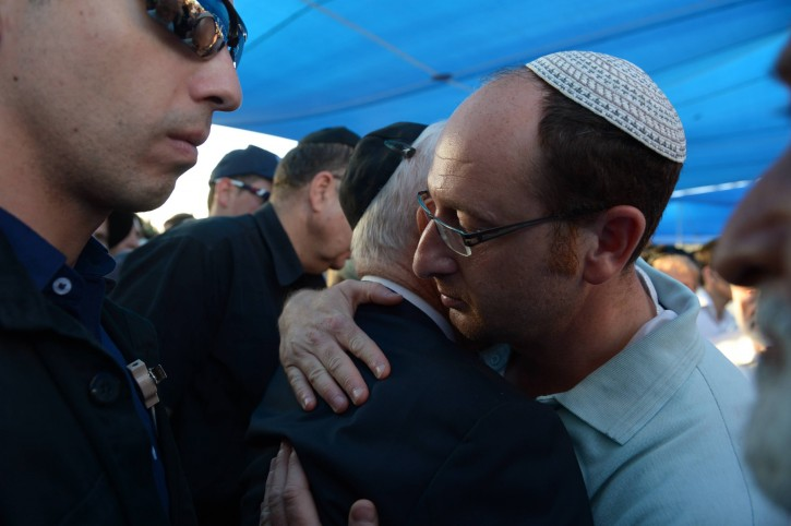President Shimon Peres embraces father of Gilad Sha'ar during the funeral ceremony of the three murdered Jewish boys in the Modiin cemetery, on July 1, 2014.