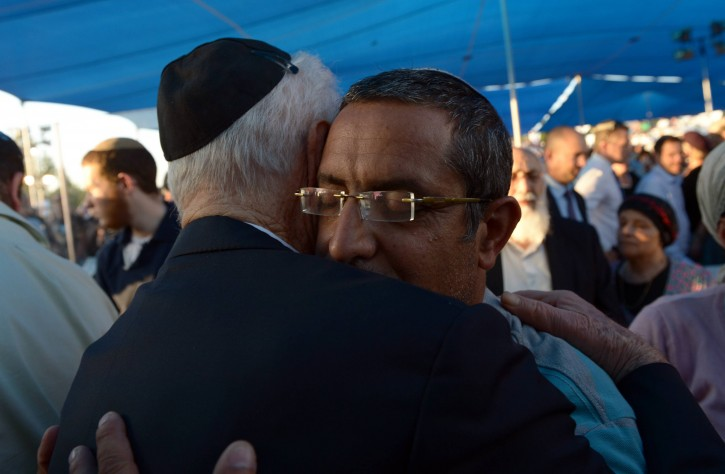 President Shimon Peres embraces a father of one of the three murdered Jewish boys during the joint funeral ceremony at the Modiin cemetery, on July 1, 2014.