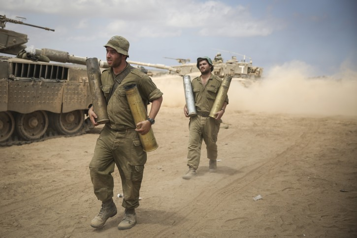 Israeli soldiers seen carrying tank emmo in a gathering point in a field near the Israeli border with Gaza, on July 25, 2014.  Flash90