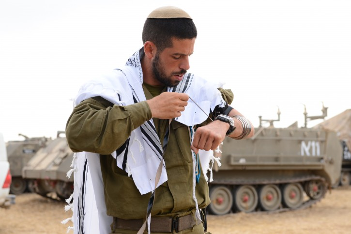 An Israeli soldier wears a prayer shawl during morning prayers at a staging area near the border with Gaza, on July 28, 2014.  Flash90