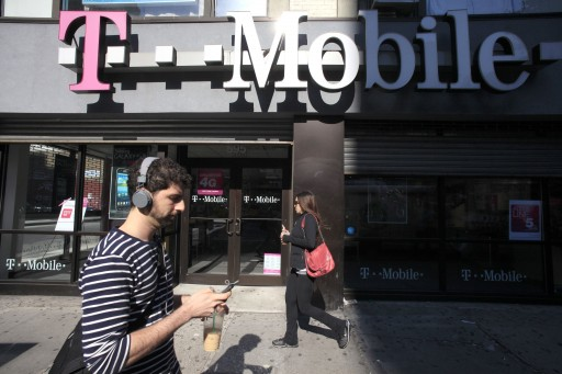 FILE - This Sept. 12, 2012 file photo shows a man using a cellphone as he passes a T-Mobile store in New York. (AP Photo/Mark Lennihan, File)