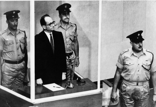 FILE - The 1961 file photo shows Adolf Eichmann standing in his glass cage in the Jerusalem courtroom where he was tried for war crimes committed during World War II. Germany's highest court has rejected a newspaper's suit against a ruling that the country's foreign intelligence service can keep secret parts of its files on Adolf Eichmann, known as the architect of the Holocaust.