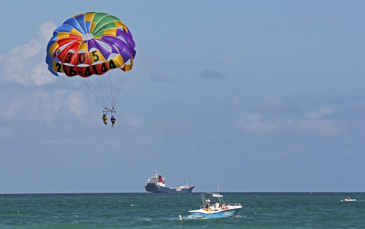 In this Sept. 24, 2012 file photo shows a couple parasailing off Miami Beach, Fla.  Parasailing is risky and should be better regulated by the Coast Guard and other entitites, the National Transportation Safety Board concluded in a report issued Tuesday, July 1, 2014. (AP Photo/Tony Winton, File)