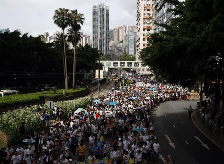 Tens of thousands of pro-democracy protesters stage a march to demand universal suffrage in Hong Kong July 1, 2014. Pro-democracy protesters gathered for a mass march in Hong Kong on Tuesday, with one burning a photograph of the city's leader and another calling for him to be sacked, in what could be the biggest challenge to Chinese Communist Party rule in more than a decade.   REUTERS/Bobby Yip