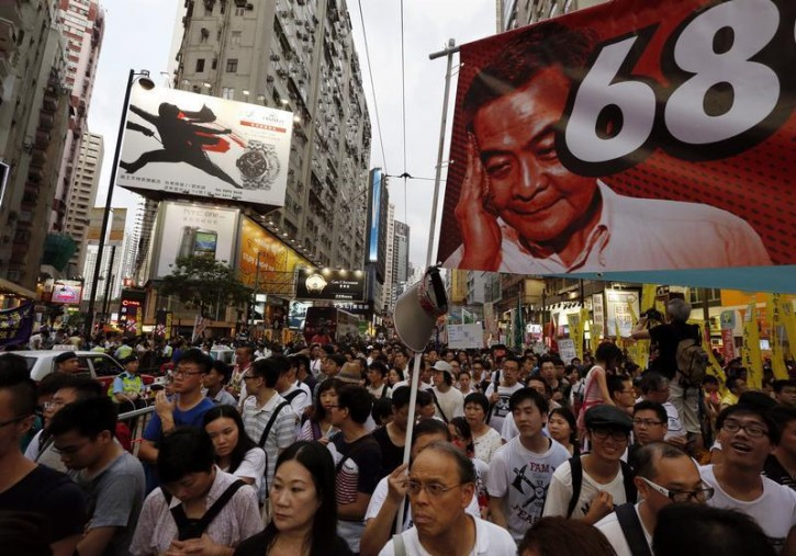 Protesters carry a banner with a portrait of Hong Kong Chief Executive Leung Chun-ying, as they join tens of thousands during a march to demand universal suffrage in Hong Kong July 1, 2014, the day marking the 17th anniversary of the territory's handover to China. Pro-democracy protesters gathered for a mass march in Hong Kong on Tuesday, with one burning a photograph of the city's leader and another calling for him to be sacked, in what could be the biggest challenge to Chinese Communist Party rule in more than a decade.   REUTERS/Bobby Yip
