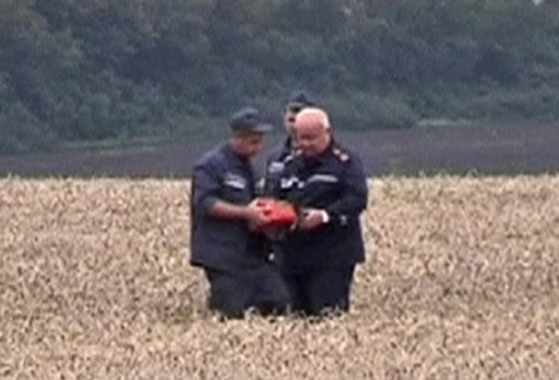 A rescue worker shows a flight data recorder to a colleague at the crash site of Malaysia Airlines Flight MH17 in Hrabove July 18, 2014 in this still image taken from video. Reuters