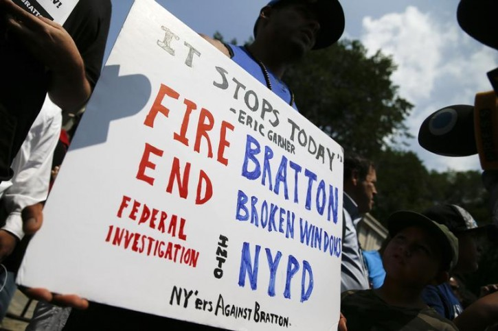 Josmar Trujillo, an activist with New Yorkers Against Bratton holds a sign outside city hall during a rally in New York July 21, 2014. The demonstration against NYPD Commissioner Bill Bratton comes four days after the death of Eric Garner, an asthmatic father of six from the borough of Staten Island, who died after New York police tackled him in front of a beauty parlor and put him in a chokehold.  REUTERS/Shannon Stapleton