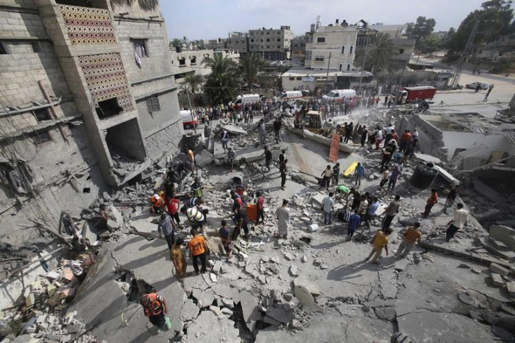 Palestinian rescue workers search for victims as people gather atop the remains of a house, which witnesses said was destroyed in an Israeli air strike, in Khan Younis in the southern Gaza Strip July 29, 2014.