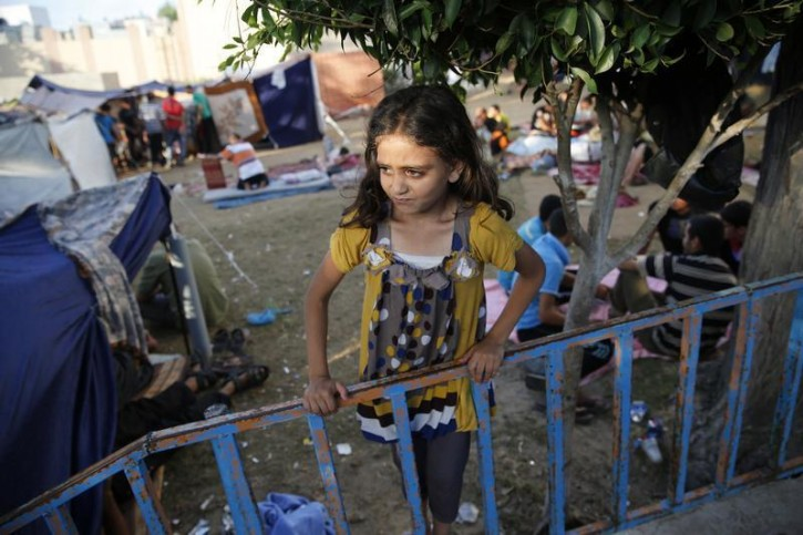 A Palestinian girl who fled an Israeli ground offensive and air strikes, stands near makeshift tents in the garden of the Shifa hospital in Gaza City July 31, 2014.
