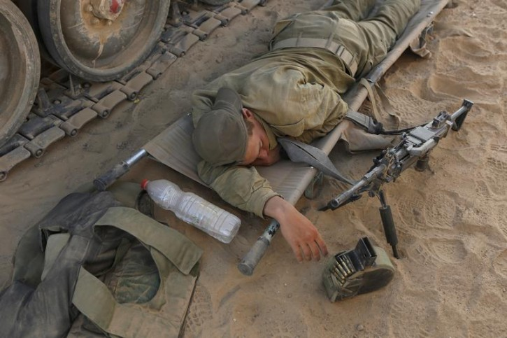 An Israeli soldier rests on a stretcher next to an armoured vehicle at a staging area near the border with the Gaza Strip July 31, 2014.  Reuters