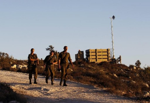 FILE - Israeli soldiers walk next to an Iron Dome missile interceptor battery as its being positioned on the outskirts of Jerusalem, September 8, 2013. REUTERS/ Ammar Awad