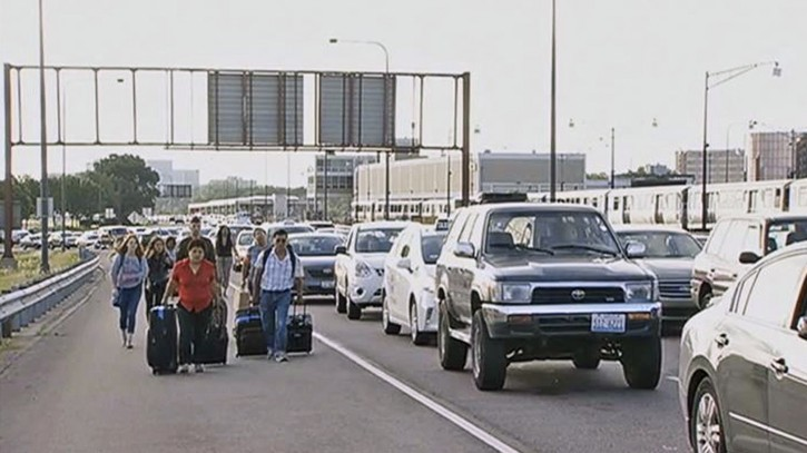 This photo from video provided courtesy of WMAQ-TV in Chicago shows air travelers wheeling their luggage toward Chicago's O'Hare International Airport Tuesday, July 1, 2014, after sudden rains flooded the Kennedy Expressway, a major thoroughfare that runs to the airport. Desperate travelers were forced to get out of taxis and haul their luggage the rest of the way to the airport. (AP Photo/Courtesy of WMAQ-TV Chicago)