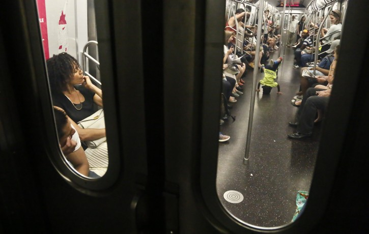 In this June 17, 2014 photo, subway riders are treated to a performance of acrobatic dancers from the dance troupe W.A.F.F.L.E., which stands for We Are Family For Life Entertainment, in New York. (AP Photo/Bebeto Matthews)
