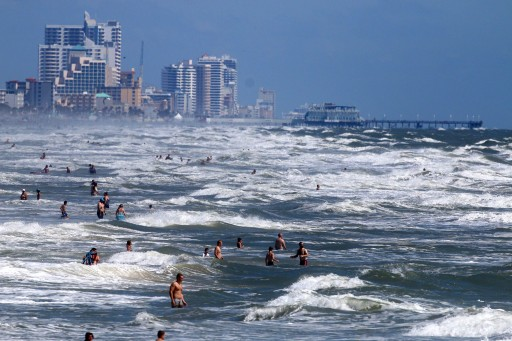 People deal with the high surf and currents off Daytona Beach generated by Tropical Storm Arthur on Tuesday, July 1, 2014.  AP