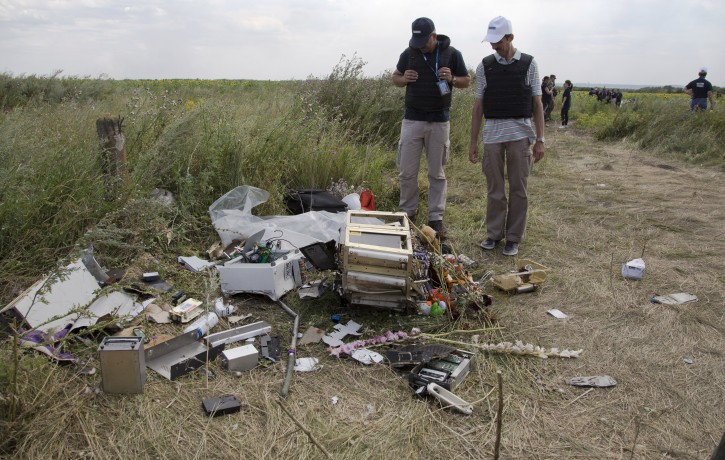 Members of the OSCE mission in Ukraine examine pieces of the crashed Malaysia Airlines Flight 17 in the village of Rassipne, Donetsk region, eastern Ukraine, Friday, July 25, 2014. (AP Photo/Dmitry Lovetsky)