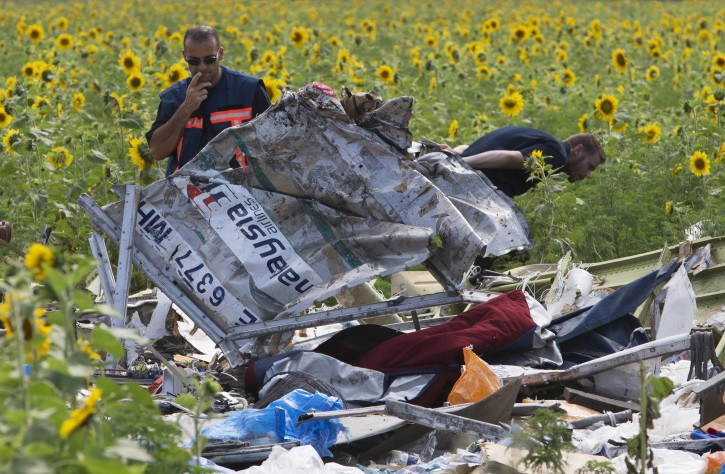 Dutch investigators examine pieces of the crashed Malaysia Airlines Flight 17 in the village of Rassipne, Donetsk region, eastern Ukraine, Friday, July 25, 2014. (AP Photo/Dmitry Lovetsky)