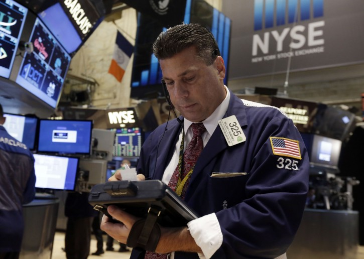 Trader William McInerney works on the floor of the New York Stock Exchange Tuesday, July 1, 2014.  (AP Photo/Richard Drew)