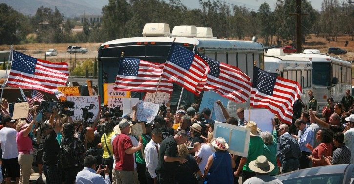 Protesters turn back three buses carrying 140 immigrants as they attempt to enter the Murrieta U.S. Border Patrol station for processing on Tuesday, July 1, 2014, in Murrieta, Calif.(AP Photo/The Press-Enterprise, David Bauman)