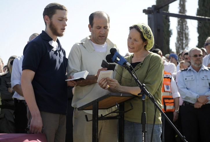 Avi (C) and Rachel (R) Frenkel and their son (L), recite Kadish close to the body of their son Naftali Frenkel, 16, (unseen) during his funeral service in the Jewish settlement of Nof Ayalon, in the Israeli  West Bank, on July 1, 2014.(AFP PHOTO/DAVID BUIMOVITCH)
