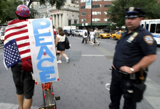 FILE-  An unidentified anti-Bush passes a New York City policeman as he circulates at Union Square in New York on Thursday, 02 September 2004 as part of the protests against the Republican National Convention. EPA