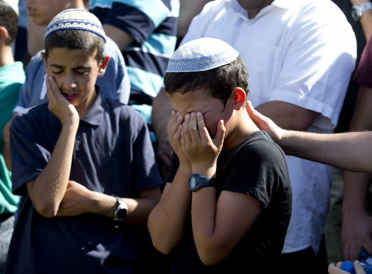 Friends of 16-year-old Naftali Frenkel, crying at his funeral service in his hometown of Nof Ayalon, Israel, 01 July 2014. Later Naftali is to be buried together with the two others teenage Israelis who were kidnapped on June 12 and soon after murdered.  EPA/JIM HOLLANDER