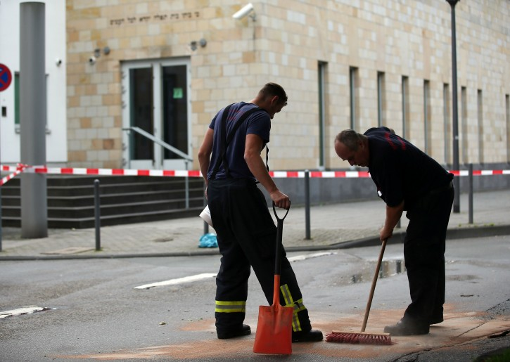 Firefighters clear away the remains of incendiary devices in front of the synagogue in Wupperetal, Germany, 29 July 2014. Three men had attacked the synagogue with several Molotov cocktails in the previous. The police said that they caught an eighteen year old suspect close to the synagogue while the two other suspects escaped.  EPA/OLIVER BERG