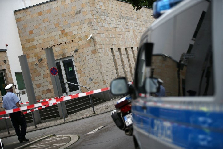 A police officer stands in front of the synagogue in Wupperrtal, Germany, 29 July 2014. Three men had attacked the synagogue with several Molotov cocktails in the previous. The police said that they caught an eighteen year old suspect close to the synagogue while the two other suspects escaped.  EPA/OLIVER BERG