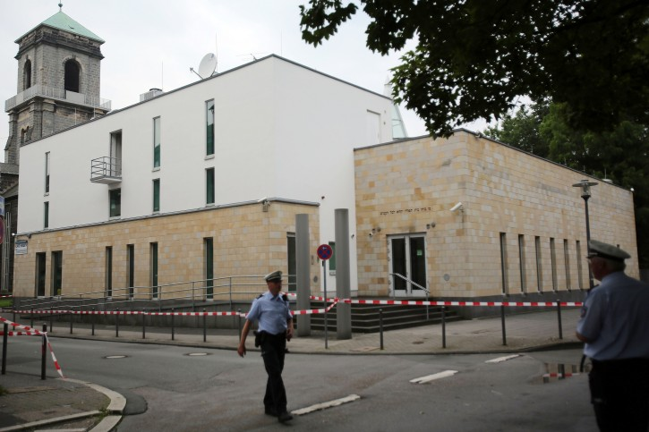 Police officers stand in front of the synagogue in Wupperrtal, Germany, 29 July 2014. Three men had attacked the synagogue with several Molotov cocktails in the previous. The police said that they caught an eighteen year old suspect close to the synagogue while the two other suspects escaped.  EPA/OLIVER BERG
