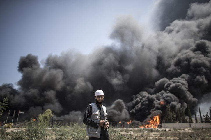 A Palestinian man walks in front of a fire raging at the Gaza's main power plant following an overnight Israeli airstrike, south of Gaza City, 29 July 2014.