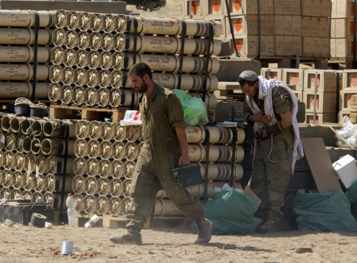 An Israeli soldier prays next to a stockpile of tank shells as another re-arms his tank at a staging area inside southern Israel along the Gaza Strip border, 31 July 2014.  EPA