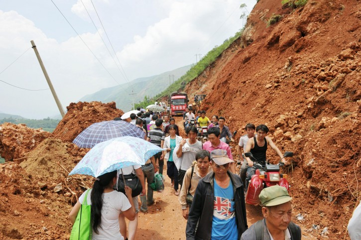 People walk through a mountain path narrowed by Sunday's earthquake in Ludian County of Zhaotong City in southwest China's Yunnan Province, Monday, Aug. 4, 2014. Rescuers dug through shattered homes Monday looking for survivors of a strong earthquake in southern China's Yunnan province that killed hundreds and injured more than a thousand people. (AP Photo/Kyodo News)
