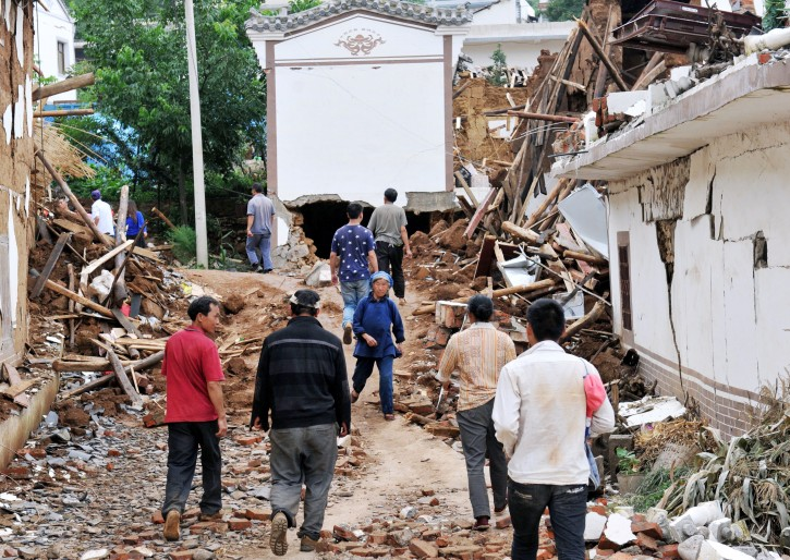 People walk by collapsed houses  after Sunday's earthquake in Ludian County of Zhaotong City in southwest China's Yunnan Province, Monday, Aug. 4, 2014. Rescuers dug through shattered homes Monday looking for survivors of a strong earthquake in southern China's Yunnan province that killed hundreds and injured more than a thousand people. (AP Photo/Kyodo News)