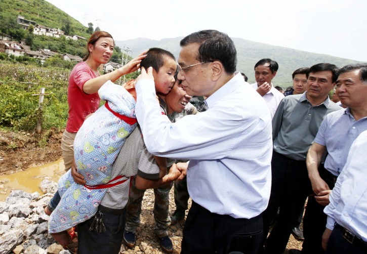 Chinese Premier Li Keqiang comforts a child at the earthquake zone in southwest China's Yunnan Province, Aug. 4, 2014. Premier Li Keqiang walked into Longtoushan Township of Ludian County Monday to examine the situation of the earthquake and instruct the quake relief work. (Xinhua/Yao Dawei) (yxb)